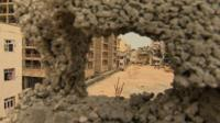 View through hole in damaged Benghazi wall