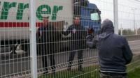 Migrant gestures at police