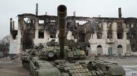Tank in Vuglegirsk, Ukraine in front of destroyed building