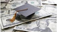 A graduation cap on top of US bank notes