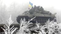 Ukrainian servicemen ride on a tank