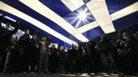 Protesters hold a giant Greek national flag during an anti-austerity and pro-government demonstration in front of the parliament in Athens on 15 February 2015