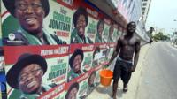 A man walk past campaign posters of Nigerian President Goodluck Jonathan and candidate of the ruling People's Democratic Party in Lagos on 21 March 2015