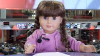 American Girl doll reading the news