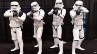 Fans dressed in costume pose on the opening day of the 25th Star Wars Convention in California
