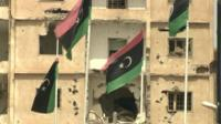 Badly damaged building and Libyan flags