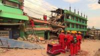 Rescue workers in front of a collapsed building