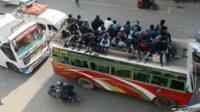 Nepalese people travel on bus roof tops as they leave Kathmandu fearing an epidemic or fresh tremers in Kalanki on the outskirts of Kathmandu