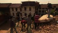 People digging through the rubble