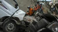 Workers picking through wreckage and rubble