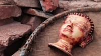 Buddha mask in rubble