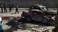 Afghan and foreign security forces inspect the site of the attack
