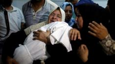 A relative mourns as she carries the body of 8-month-old Palestinian infant Laila al-Ghandour