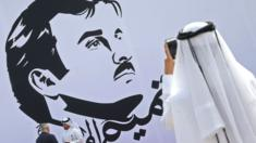 Qatari man takes a photo during the inaugural signing of a wall bearing a portrait of Qatar's Emir Sheikh Tamim bin Hamad Al Thani in Doha on 13 July 2017