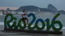 A person sits on a sign for the Rio 2016 Olympics at dawn in the Copacabana neighbourhood of Rio de Janeiro