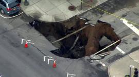A giant sinkhole opens up a residential street in the New York neighbourhood of Brooklyn
