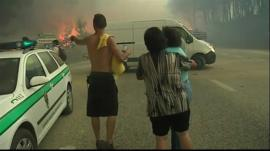 People watch as their homes get destroyed by fire
