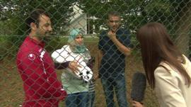 The BBC's Jenny Hill (far right) speaks to a family from Syria in Germany