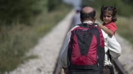 A man hoping to cross into Hungary, carrying a child just outside the village of Horgos in Serbia