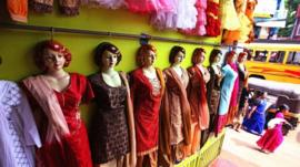 Picture shows a row of mannequins wearing traditional clothes.
