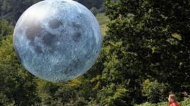 girl looking at moon balloon