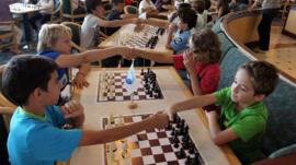 Children shake hands before a chess tournament starts
