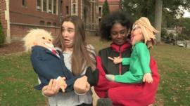 Children holding felt dolls of Donald Trump and Hillary Clinton
