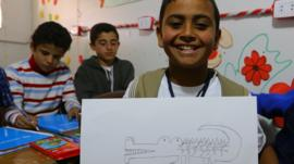 Syrian refugee with his drawing