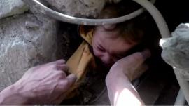 Child being pulled from rubble in Syria