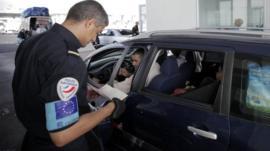 Frontex guard checks passport, file pic