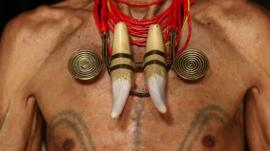 An Indian headhunter showing off his tattoos