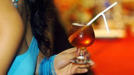 امرأة تحمل كأسا