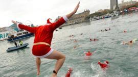 سكان من مدينة برشلونة بملابس بابا نويل يقفزون في ماء البحر.