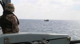 Military personnel on ship watching over small ship in sea