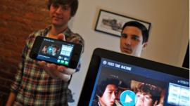 The creators of Video Time Machine holding an iPhone and iPad