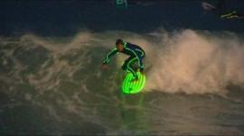 A surfer wearing a wetsuit that glows in the dark - on Bondi Beach in Australia