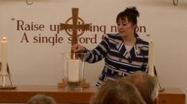 Margaret Allen lights the candle of remembrance