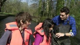 Joe with schoolchildren by a river