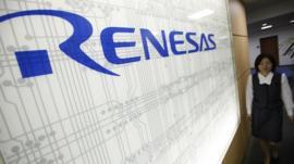 Worker next to logo of chipmaker Renesas Electronics