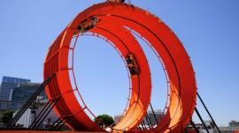 Two cars do a loop the loop on 18 metre high rings