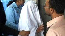 Rimsha with a blanket over her head being escorted by a policewoman