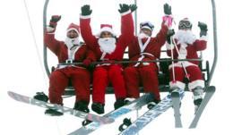 People dressed as Santa on a ski lift.