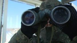 A soldier looks through binoculars