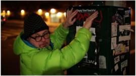 A man affixes a protest sticker to a utilities box