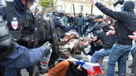 Riot police spray teargas on demonstrators during a demonstration against France