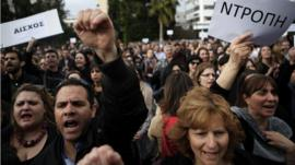 Employees of the Bank of Cyprus shout slogans as they holds banners reading in Greek