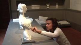 A woman touching a copy of a sculpture