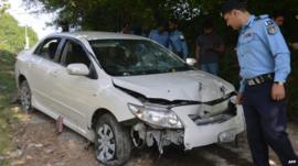 Pakistani police officials examine the bullet-riddled car of Chaudhry Zulfiqar