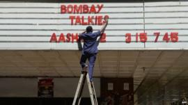 An employee of the New Excelsior Theatre puts up letters spelling out the movie