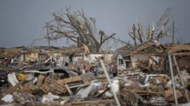 People assess the damage after a powerful tornado ripped through Moore, Oklahoma